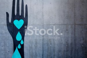 hand holding blue bleeding heart on concrete background