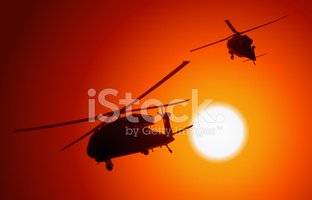 UH-60 Blackhawk transport helicopters passing by as the sun sets